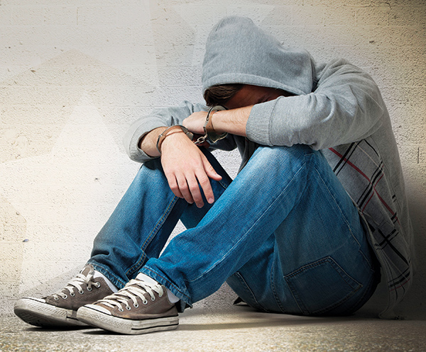 A handcuffed teen sits on with his arms covering his face.