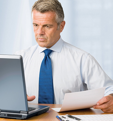 A man looks at a computer while holding a piece of paper.