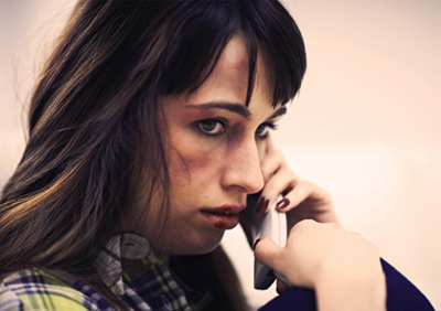 A battered woman holds a phone