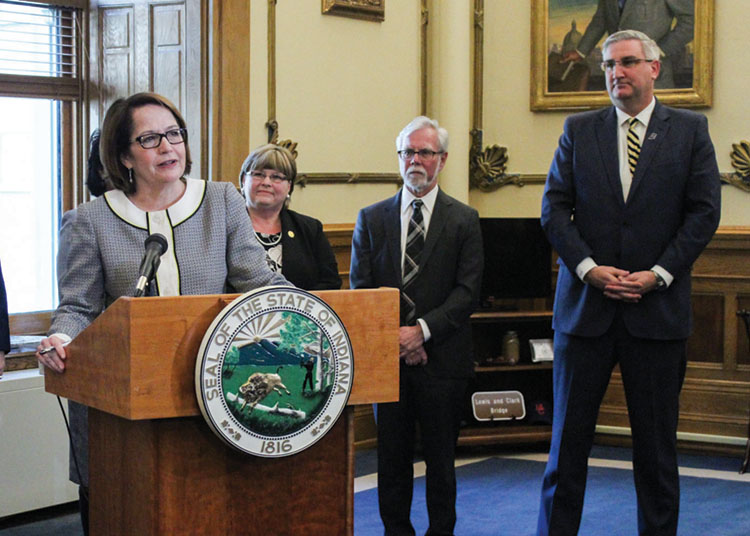 Chief Justice Loretta Rush stands at a podium