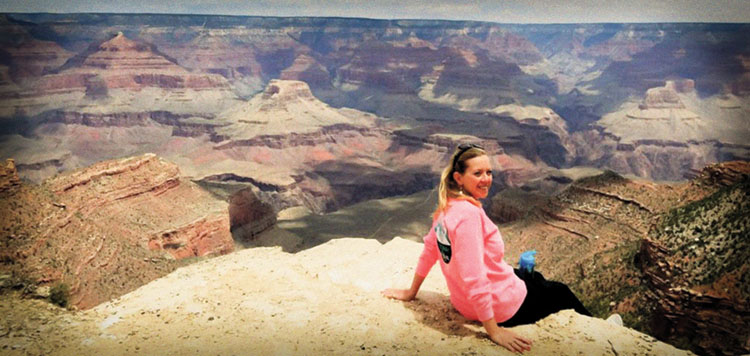 Judge Andrea K. McCord sits on the edge of the Grand Canyon