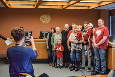 enior Judge Gerald Zore and a family are photographed following an adoption proceeding in Marion County.