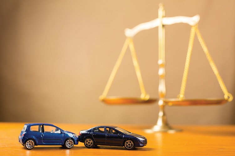 Toy cars involved in a collision are featured in the foreground of an image with gold scales of justice in the background.