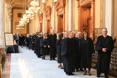 Indiana trial court judges stand in the hallway of the State House as they wait to enter the gallery of the Indiana House of Representatives.