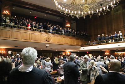 Judges and representatives applaud Indiana trial court judges as they stand in the gallery of the Indiana House of Representatives.