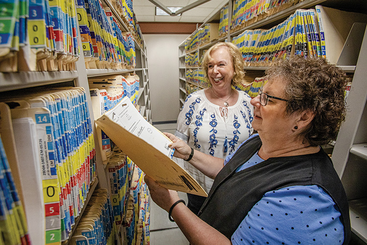 Clerks smile while standing amid shelves of old paper records