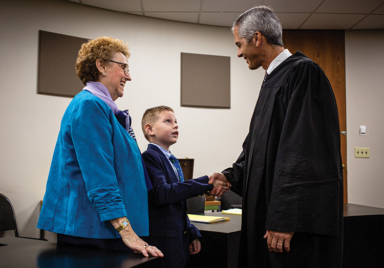 A judge shakes the hand of a little boy dressed in a suit the day he was adopted by his grandmother, also pictured..