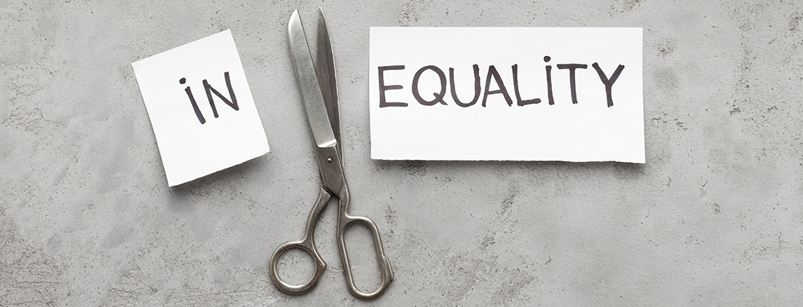 """Scissors have cut the word """"inquality"""" printed on paper, and the words """"in"""" and """"equality"""" remain"""