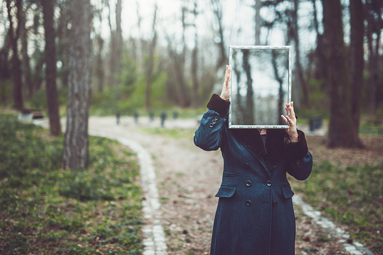 Woman stands holding a mirror where her face should be