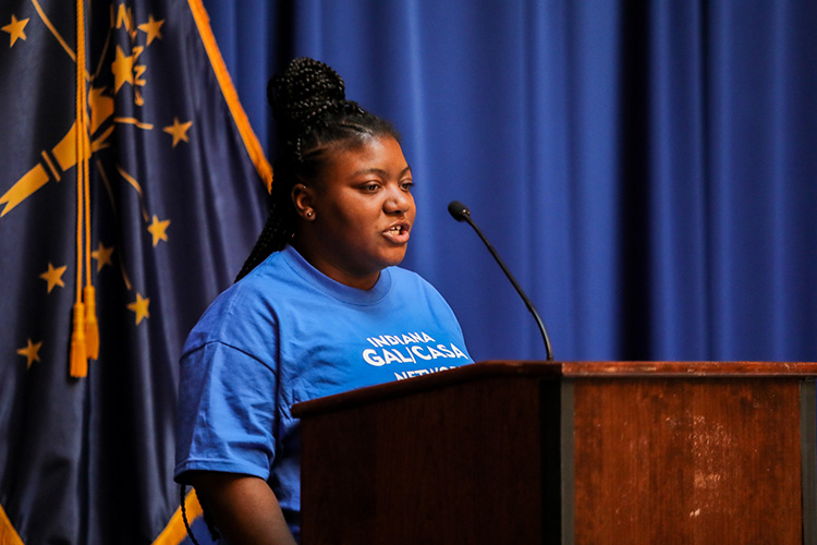 Former foster youth De'Coriyanna Garrett stands behind a podium at the Indiana State House during CASA Day.