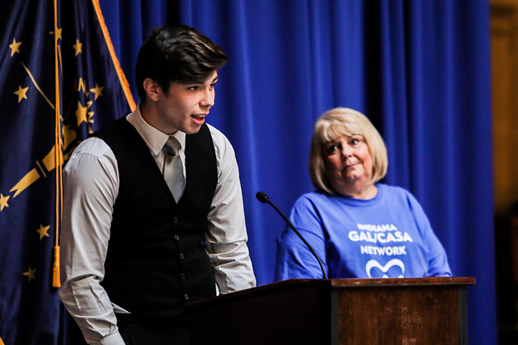 Kenneth stands behind a podium alongside his CASA, Linda Brown, during CASA Day at the Indiana State House.
