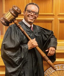 Judge Geoffrey Gaither holds an oversized gavel in front of a courtroom bench.