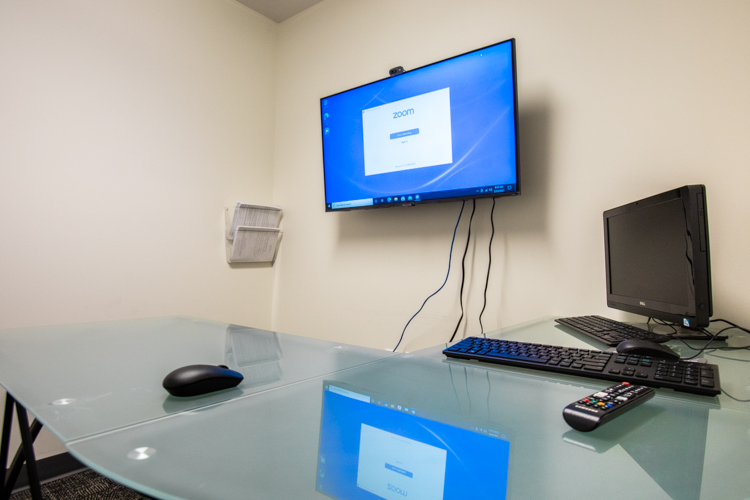 A TV displaying videoconferencing software is mounted in a wall above a desk.