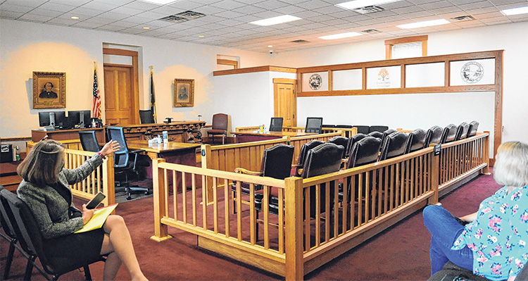 Two people sit socially distanced in a courtroom.