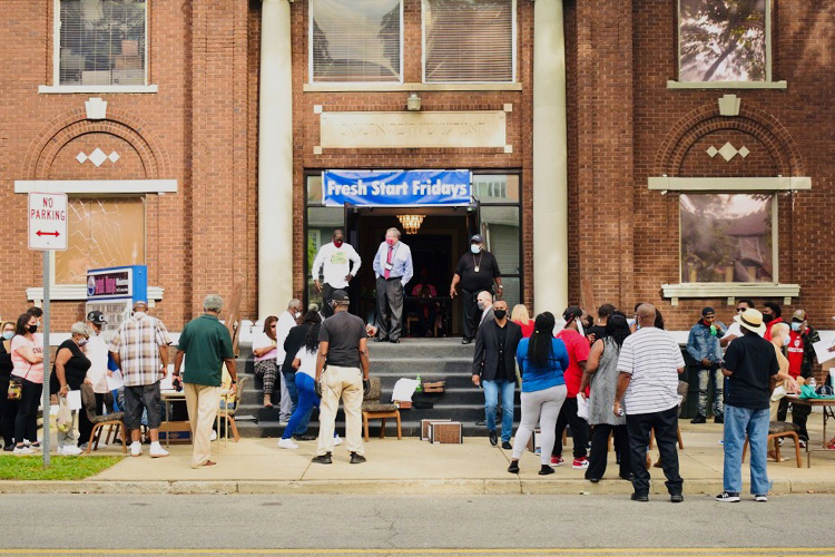 """People crowd a sidewalk outside of a brick church. A blue banner hangs over the steps of the entryway reads, """"Fresh Start Friday."""""""