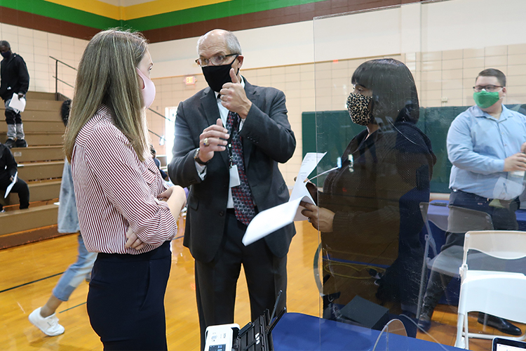 People wearing masks gather in a gymnasium to get help with expungements.