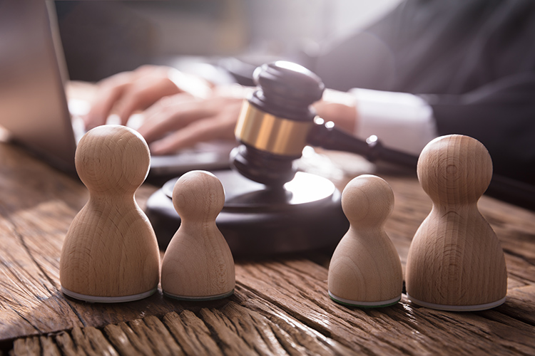 Four wooden pawn figures, two large, two small, representing a family. A gavel sits behind the figures. A person types on a computer behind the gavel.